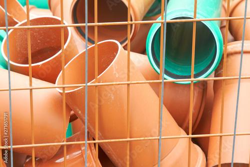 Valokuva  Ein Haufen kurzer Rohre aus Kunststoff liegt in einer Gitterbox.