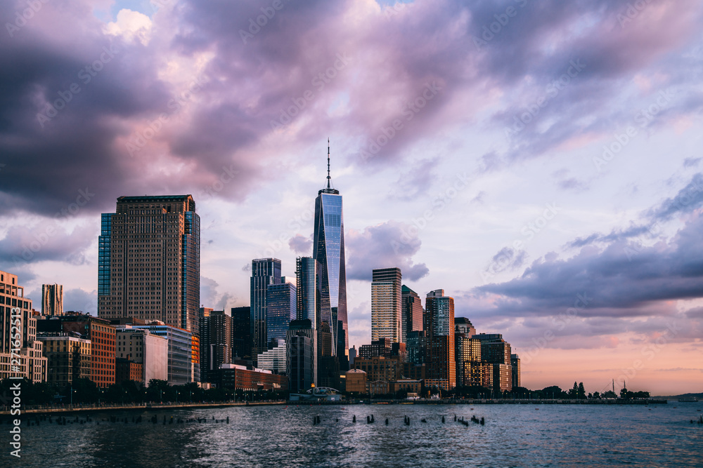 Fototapety, obrazy: Panoramic view of Manhattan Island with buildings and Hudson river. Scenery skyline view of contemporary glass skyscrapers of downtown financial district in New York. Dramatic sunset sky over city