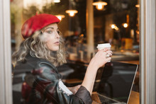 Beautiful Young Female In Red Beret Drinking Hot Beverage And Looking Out Window While Browsing Laptop In Cafe