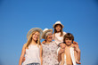 Smiling grandmother and grandchildren in hats and summer wear standing together in sunny day
