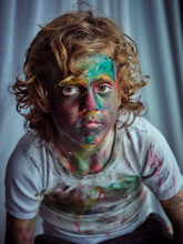 Cute Funny Boy Painted In Bright Paints Sitting Near Curtains And Drawing On Face
