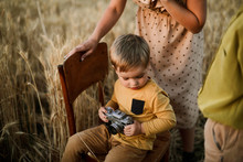 Son Photographing With Vintage Camera By Mother And Brother At Sunset