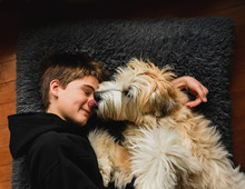 Boy Laying On Floor On Pillow With Dog While It Licks Him On The Nose.