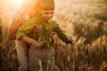 A Mother And Son Playing Together In The Wheat Fields During Sunset