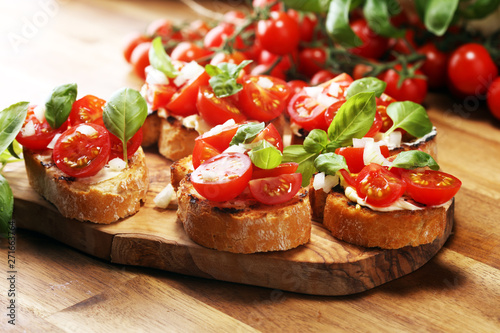 Photo  Traditional italian antipasto bruschetta appetizer with cherry tomatoes, cream cheese, basil leaves and balsamic vinegar on cutting board