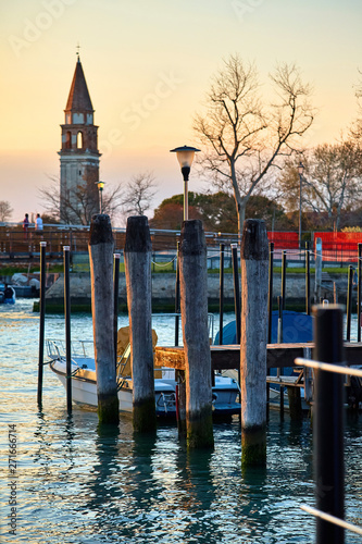 Venice, Italy. Sunset evening. View at tower and Pier and landing with boat at water. Autumn landscape.