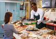 Salesman serving customer raw fish