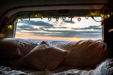 Camper Van With Cushion And Fairy Lights, View Through Rear Window At Sunset.