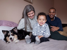 Portrait Of Cute Smiling Son Sitting With Parents And Dog On Bed Against Wall At Home