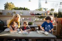 Mother Teaching Boys Kneading Pizza Dough On Table Against Sky In Yard