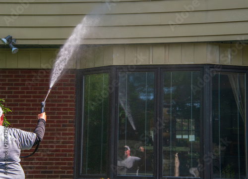 Man is seen with a spray nozzle in his hand  He is spraying