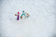 Happy snowman couple and snowman child with Christmas gift standing in winter Christmas landscape. Merry Christmas and happy New Year. Funny snowman family in stylish hat and scarf on snowy field.