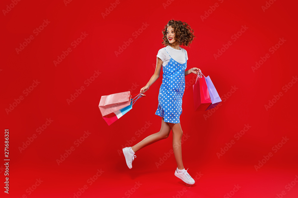 Fototapeta concept of shopping purchases and sales of happy young girl with packages  on yellow background.