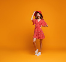 Concept Happy Emotional Young Woman In Red Summer Dress And Hat Jumping   On Yellow Background