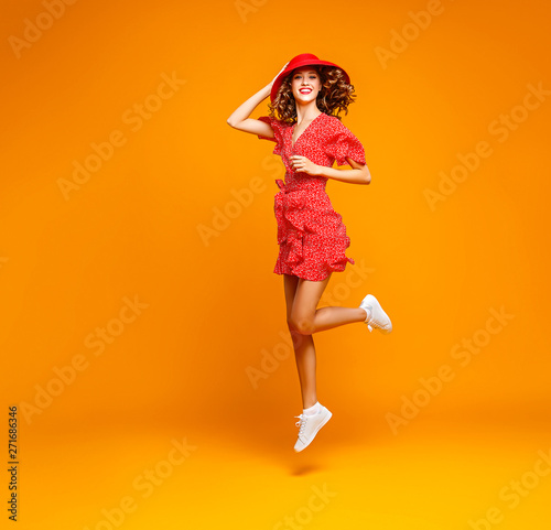 Fotografia  concept happy emotional young woman in red summer dress and hat jumping   on yel