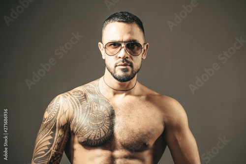 Fotografie, Tablou  Muscular macho man with athletic body in sunglasses