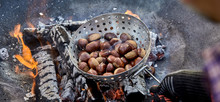 Panorama Banner Of A Man Roasting Fresh Chestnuts