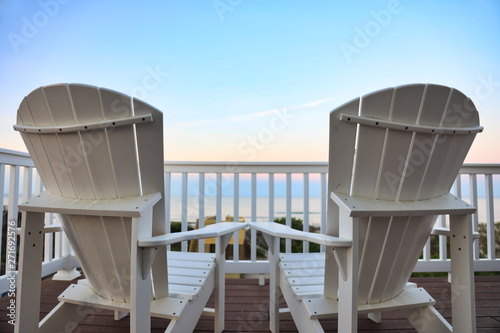 relax on Adirondack chairs in a desk balcony overlooking the beach and  ocean at sunset Wallpaper Mural