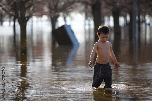 Fotomural Young toddler plays in water of flooded park after heavy rain storm