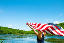 4th Of July. Young Woman Holding American Flag On Lake Background.