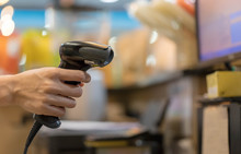 Close Up Barcode Scanner In Hand On Blurred Background,Inspection Of Goods In The Warehouse,The Concept Of Selling Products In A Supermarket,Spot Focus,Copy Space.