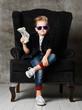 Leinwandbild Motiv Young rich boy kid millionaire sits in big luxury armchair and demonstrates bundle of money dollar bills