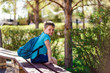happy smiling schoolboy with backpack sitting on bench