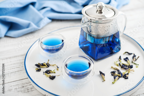 Photo  Two glass cup of blue Anchan tea with teapot