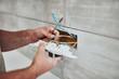 Leinwanddruck Bild - Electrician repairing / fixing wires in the wall.