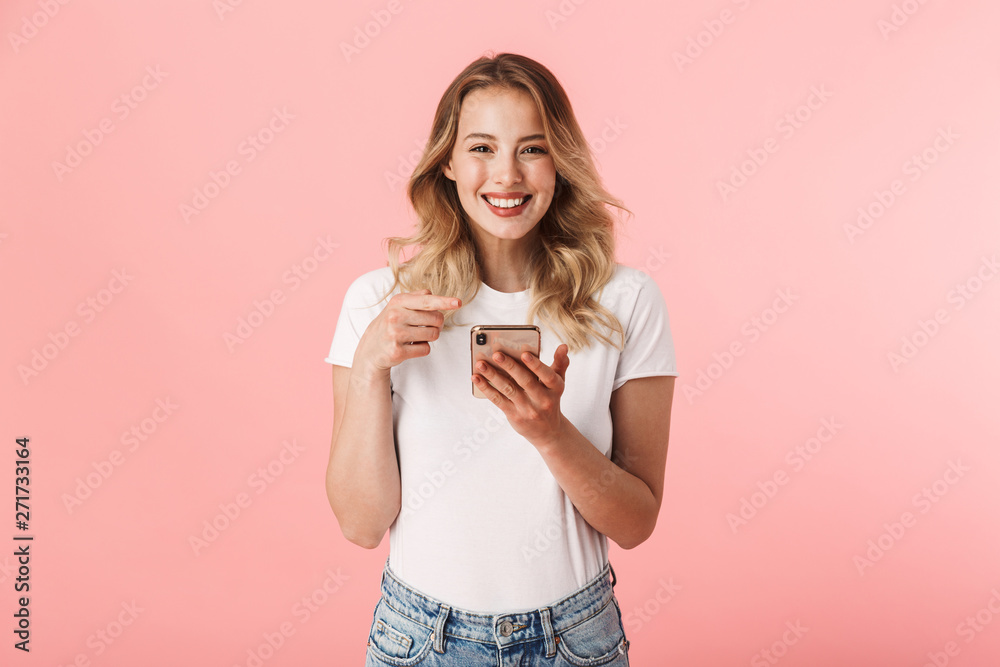 Fototapeta Happy young blonde woman posing isolated over pink wall background using mobile phone.