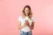 canvas print picture - Happy young blonde woman posing isolated over pink wall background using mobile phone.