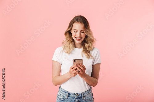 Happy young blonde woman posing isolated over pink wall background using mobile phone Tablou Canvas