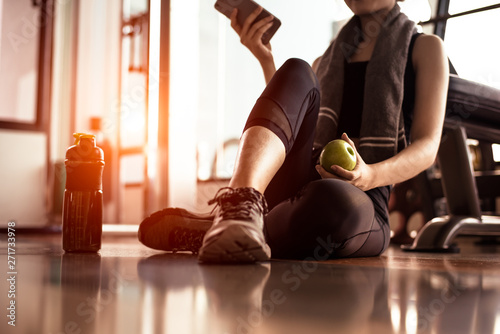 Deurstickers Fitness Close up of woman using smart phone and holding apple while workout in fitness gym. Sport and Technology concept. Lifestyles and Healthcare theme.