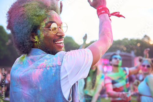 Poster Echelle de hauteur African man in holi colors dancing during music festival
