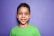 Portrait of cute little boy on color background
