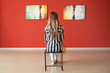 canvas print picture - Woman sitting on chair in modern art gallery