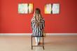 Leinwanddruck Bild - Woman sitting on chair in modern art gallery
