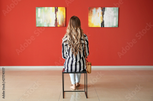 Fotomural Woman sitting on chair in modern art gallery