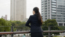 Back View Relax Woman Manager Standing On Balcony Modern Office Overlooking City Center Leaning On Railing. Female Asian Ceo In Suit Enjoy Urban Park Fresh Air With Skyscraper In Back. Real Moments