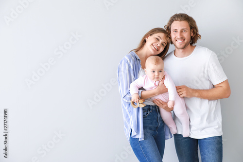 Obraz Happy parents with cute little baby on light background - fototapety do salonu