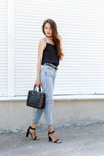 Young Stylish Woman Wearing Black Cami Silk Top, Blue Cropped Denim Jeans, Black High Heel Sandals And Holding Black Handbag Posing Against White Street Wall. Trendy Casual Outfit. Street Fashion.