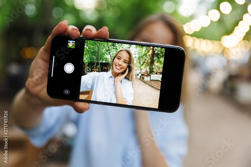 Valokuvatapetti Excited happy young woman posing outdoors in park take a selfie by mobile phone