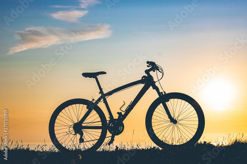 Tuinposter Fiets beautiful sunset on the sea and the silhouette of a bicycle