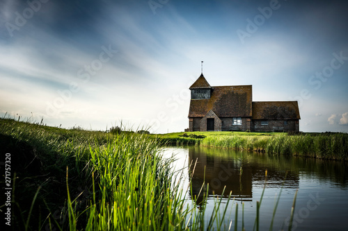Photo Stands Roe English church reflected in waterway in Kent