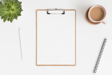 Top View Of A Wooden Clipboard Mockup With A Succulent Plant And Workspace Accessories On A White Table.