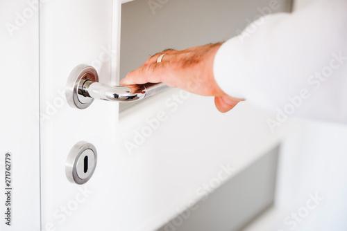 Photo  Door PVC. Hand holds doorknob.