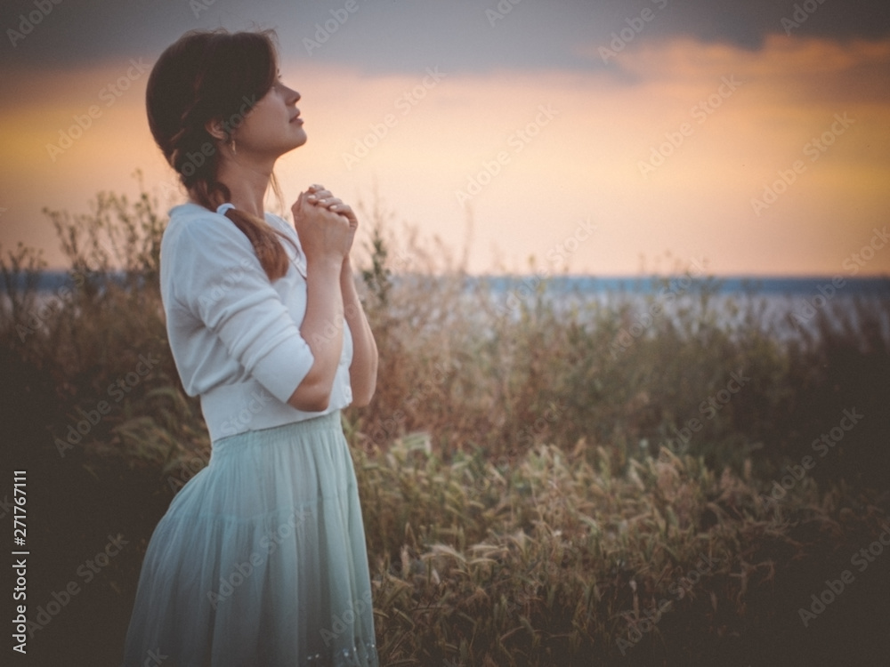 Fototapety, obrazy: silhouette profile of a beautiful girl in a dress praying to God in the field, a young woman walking on nature during sunset looking up into the sky, religion concept