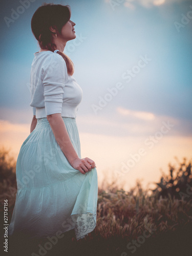 Silhouette Profile Of A Beautiful Girl In A Dress In The Field Enjoying The Sky During Sunset A Young Woman Walking In Nature The Concept Of Beauty And Harmony Buy This