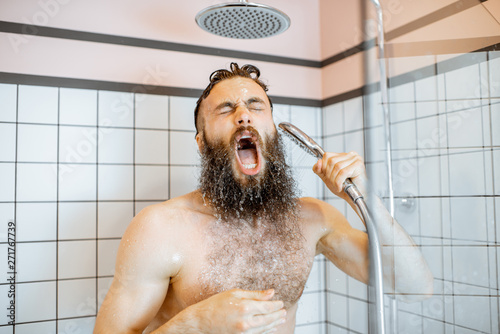 Tela Bearded man feeling shocked while taking a shower with cold water in the bathroo