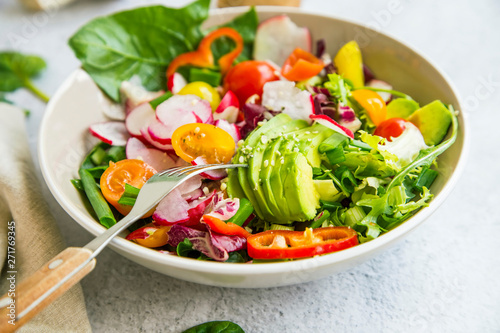 Fresh vegetable salad bowl closeup, healthy organic vegetables salad with radish, spinach, tomatoes, onion, avocado
